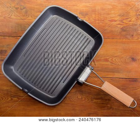 Top view of empty grill pan rectangular shape with wooden handle, non-stick coating and a series of parallel raised ridges on an old wooden rustic table stock photo