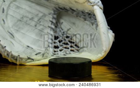 Hockey puck with the inscription `Czech Republic` on the golden background in front of goalie catcher.Black puck on golden background in front of white goalie catcher.  stock photo