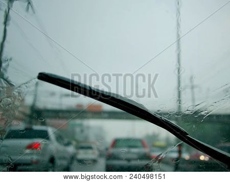 Windscreen wiper arm and blade removing rain from the windscreen stock photo