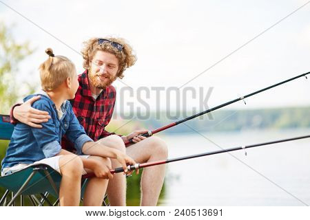 Young man with fishing rod embracing his son or buddy while sitting by lake and talking stock photo