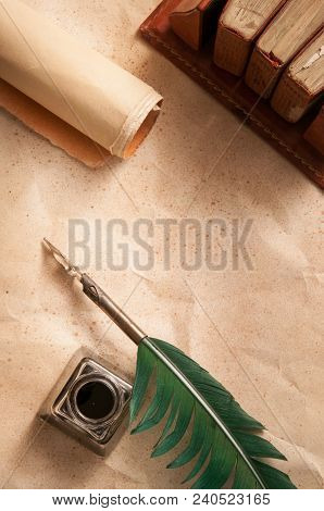 Green quil pen and black inkwell with old papers and books stock photo