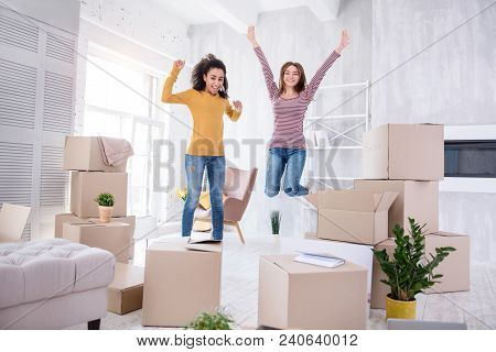 Happy to move in. Upbeat young girls jumping happily in the living room of their new apartment before unpacking boxes with their belongings stock photo