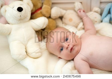 Baby boy and his white teddy bear. Childhood and curiosity concept. Baby lying on white duvet. Infant with blue eyes and interested face on light blanket with toys on background, defocused stock photo
