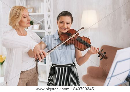 Basics of violinist. Competent tutor standing in semi position while teaching her student stock photo