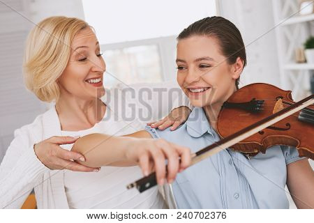 Sincere smile. Charming girl expressing positivity, learning to play the violin stock photo