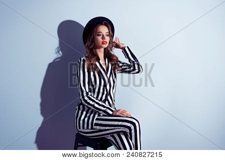 Half-turned portrait of graceful stunning exquisite posh self-assured famous popular wealthy luxurious classy lady diva with long curly hair dressed in catchy clothes isolated on gray background stock photo