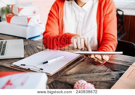 Beautiful young asian business owner working with computer and tabet smiling while standing in workshop.Responding on business e-mail,writing the order of product customer orders. stock photo