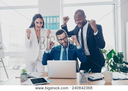 Three cheerful, full of happiness, professional, lucky experts celebrating a victory, income growth of their company, having raised arms, looking at screen of computer in workplace stock photo