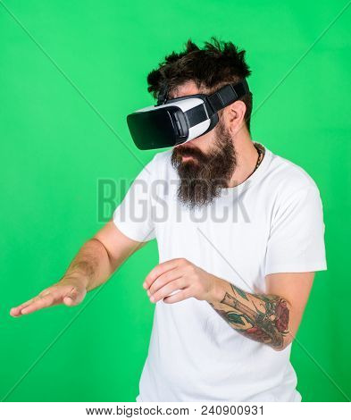 Man with beard in VR glasses, green background. Hipster on busy face use modern technologies for entertainment or education. VR musician concept. Guy DJ with VR glasses play music with mixing console. stock photo