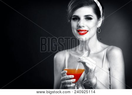 Pin up retro girl drink bloody Mary cocktail. Black and white photos with red color accents. Pin-up retro female style. Girl vintage style wearing dress. Black and white retro portrait with red accent stock photo