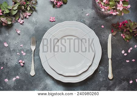 Spring elegant table place setting with romantic pink flowers, silverware on vintage background. Top view. stock photo