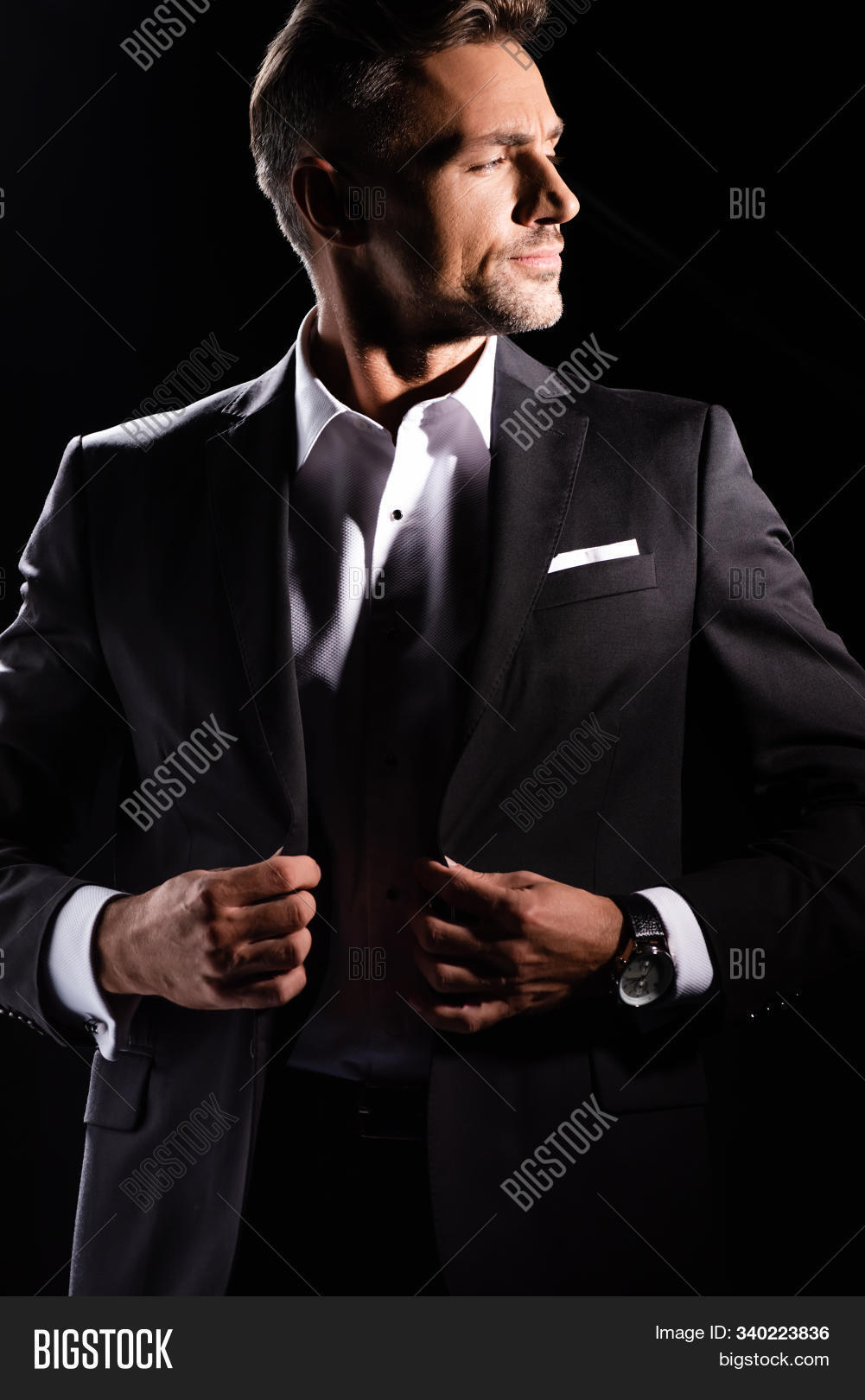 Handsome businessman adjusting lapels of jacket and looking away isolated on black