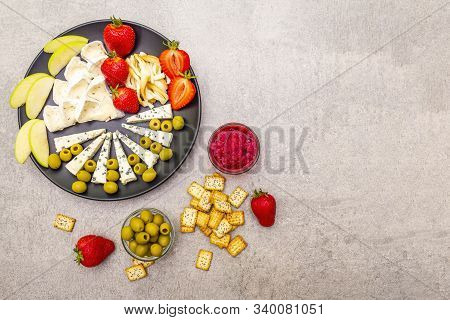 Delicious snack assorted cheeses plate. Bavarian cheese with jalapeno peppers, blue mold cheese and smoked pigtail cheese, fruits and olives, jam, crackers. On stone background, close up stock photo