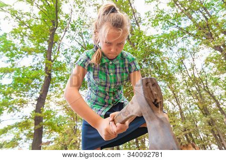 Angry and serious girl with an ax chopping wood in the forest, wide-angle photo view from below. stock photo