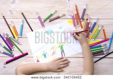 A child draws a birthday card with his family. Drawing made by a child with colorful felt-tip pens and pencils. Happy family. Childs drawing stock photo