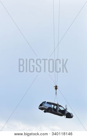Discarded old car without wheels, lifted up by cables against a sky before recycling, with text space. The concept of car updates, consumption, old age, uselessness stock photo