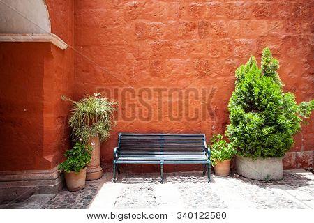 Bench near the wall, near trees in pots, Saint Catalina, Arequipa, Peru stock photo