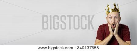 Young man with a crown on his head and a surprised face on a light background. Concept is king, luck, gain, rich, dream, goal, aspiration. Banner stock photo