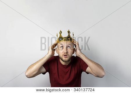 Young man with a crown on his head on a light background. Concept is king, luck, gain, rich, dream, goal, aspiration.  stock photo