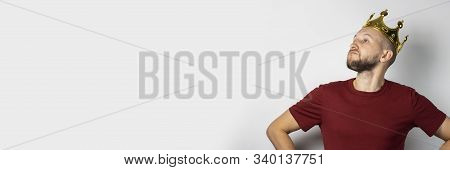 Young man tries on a golden crown on a light background. Concept is king, luck, gain, rich, dream, goal, aspiration.  stock photo