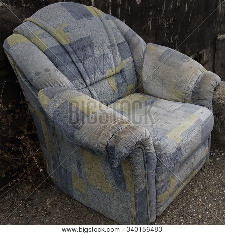 Old abandoned armchair. Blue armchair. Grunge armchair. stock photo
