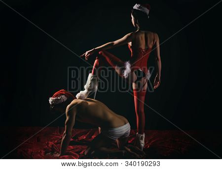 BDSM games with domination and submission. Young naughty lady with Santa hat sitting on top of her lover. Dominantning in the foreplay sexual game. Bed in dark room stock photo