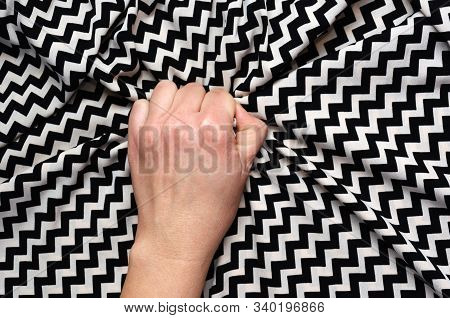 Female hand grasping or clutching silk bed sheet with geometric print in ecstasy. Sex, orgasm, sexual pleasure concept stock photo