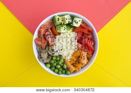 Vegan poke bowl with couscous  and vegetables in the white bowl in the center of the bicolor background. Top view. Copy space. Closeup. stock photo
