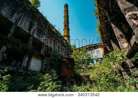 Overgrown ruins of industrial building. Abandoned, destroyed by war power plant in Tkvarcheli Tquarhcal, Abkhazia, Georgia stock photo