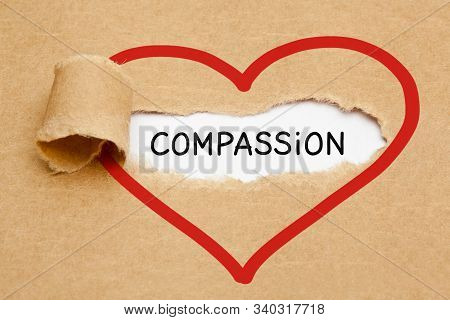 Handwritten word Compassion appearing behind ripped red heart on brown paper. stock photo