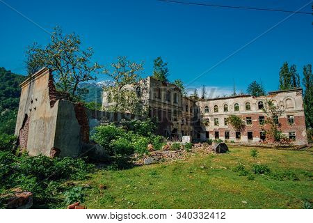 Ruined overgrown school in ghost mining town Akarmara, consequences of war in Abkhazia, green post-apocalyptic concept stock photo