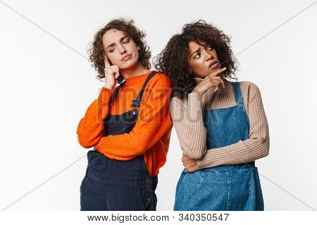 Portrait of perplexed multinational women in overalls thinking while looking upward and downward isolated over white background stock photo