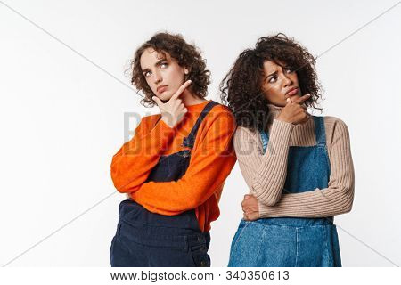 Portrait of displeased multinational women in overalls thinking and looking upward isolated over white background stock photo
