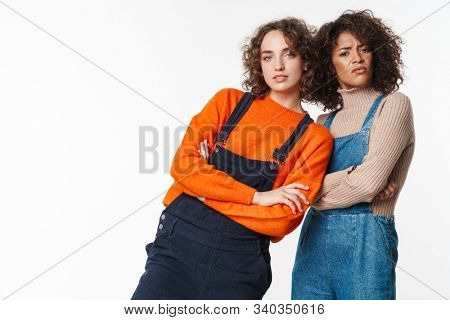 Portrait of confused multinational women in overalls looking at camera with arms crossed isolated over white background stock photo