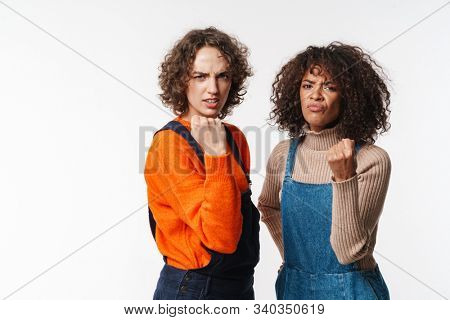 Portrait of angry multinational women in overalls showing fists at camera isolated over white background stock photo
