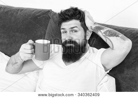 Tune in to new day. Morning awakening better with cup coffee. Relax and rest. Humanity runs on coffee. Man brutal handsome hipster relaxing bedroom drink coffee. Bearded guy enjoy morning coffee. stock photo