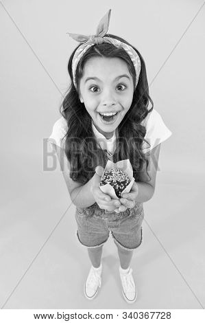Treat someone with sweets. Yummy cupcake. Homemade muffin. Sweet tooth concept. Kid girl hold appetizing muffin. Gluten free recipe. Delicious cupcake. Little child with muffin on yellow background. stock photo
