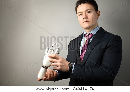 Man holds artificial limb for disabled people. Prosthetic arm. stock photo