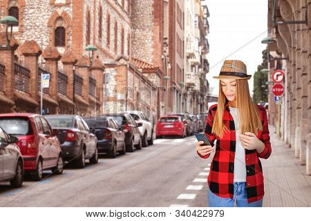 Happy Woman Walking And Using A Smart Phone On A City Street. Social Media Interactions On Mobile Ph