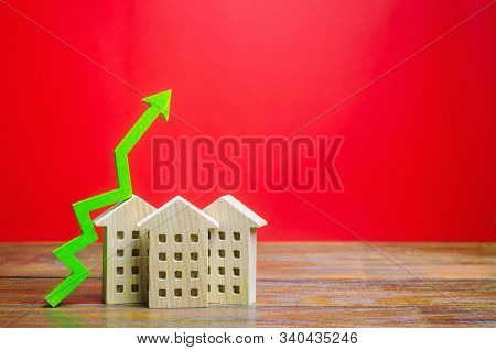 Miniature wooden houses and green arrow up. The concept of increasing the cost of housing. High demand for real estate. The growth of rent and mortgage rates. Sale of apartments. Population grows stock photo