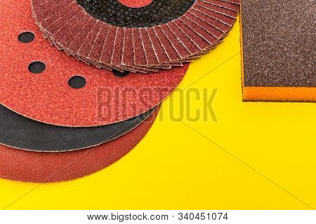 Set of abrasive tools and sandpaper on yellow background wizard is used for grinding items stock photo