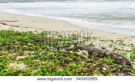 Beautiful view of the ocean with dirty beach with trashes. Big wave of blue ocean on sandy beach with plastic garbage and medical waste materials at Batu Burok Beach in Kuala Terengganu. stock photo