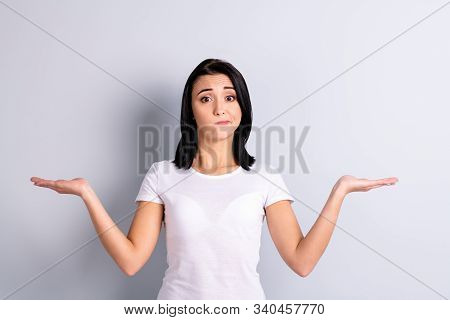 Portrait of her she nice-looking attractive lovely unsure uncertain confused girl holding two objects on palms copy empty blank space ad advert dont know isolated over light gray pastel background stock photo