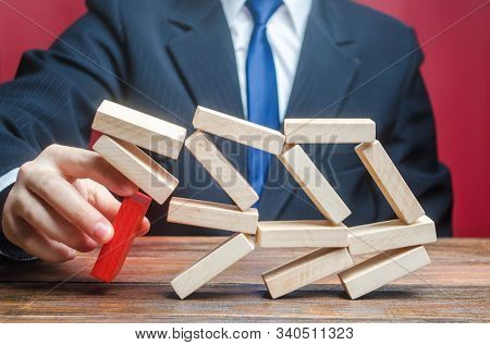 A businessman removes an important component causes collapse of entire complex system. Making wrong decisions, ruining business. Inexperience, unprofessional leader. Failure. Incompetent businessman. stock photo