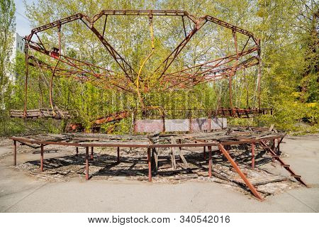 Old broken rusty metal radioactive children's electric wheel abandoned, the park of culture and recreation in the city of Pripyat, the Chernobyl disaster, Ukraine. stock photo