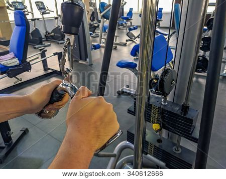 Strong man's hands pulling weight and increasing strength and endurance while body building in a modern gym while doing the weight loss regimen stock photo