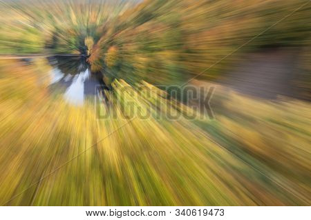 Abstract photo, A lake surrounded by autumn forest photographed with different effects of motion and zoom. Colorful textured background. long shutter speed. stock photo