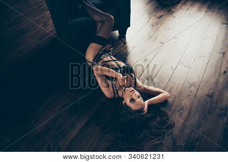 Top above high angle view of nice lovely charming gorgeous attractive stunning perfect sportive figure lady wearing swordbelt teasing lying on floor enjoying lifestyle at house loft interior wood stock photo