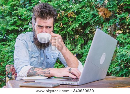 A liquid hug for his brain. Hipster enjoying coffee and free wifi in outdoor cafe. Bearded man drinking coffee and browsing the Web in coffee shop. Cyber cafe providing Internet access and hot coffee stock photo