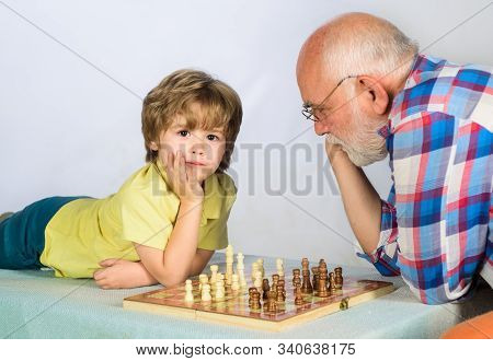 Checkmate. Little boy think or plan chess game. Child boy playing chess with grandfather. Games and activities for children. Grandfather and grandson playing chess. Little boy learning to play chess. stock photo